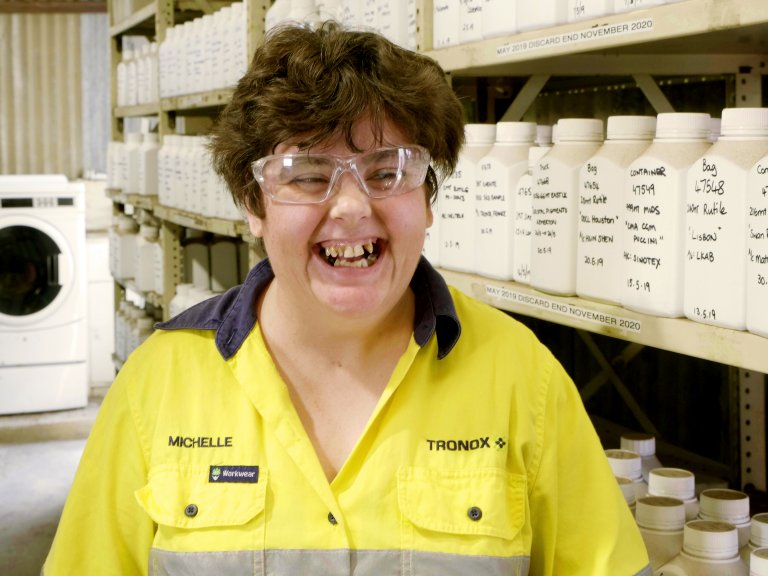 michelle smiling at camera wearing her work uniform in the workshop.