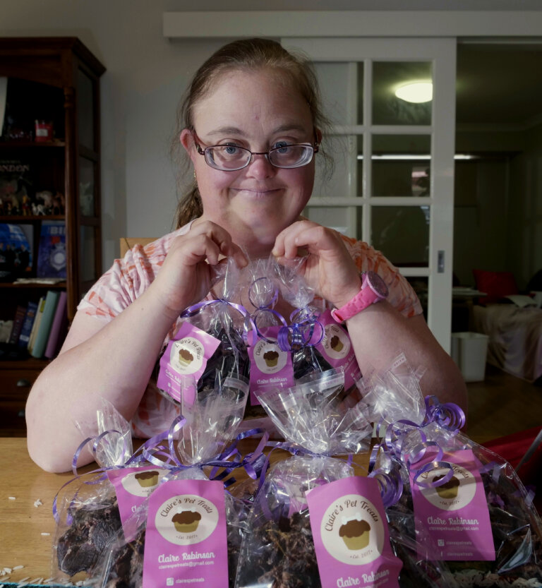 Claire sitting behind lots of packets of her pet treats