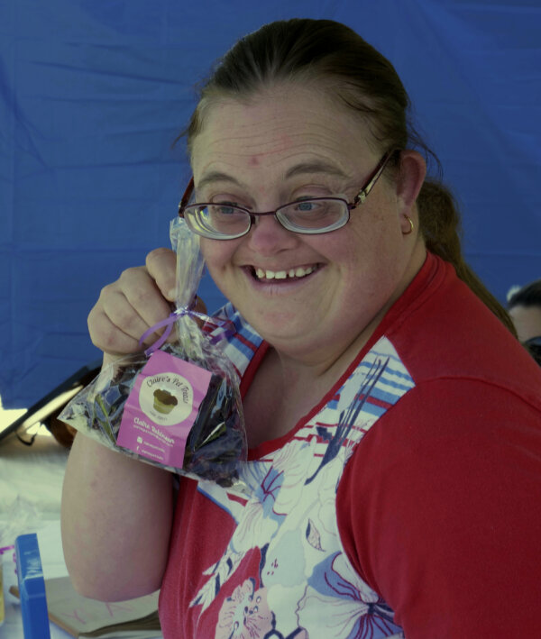 Claire smiling with a packet of her pet treats in hand