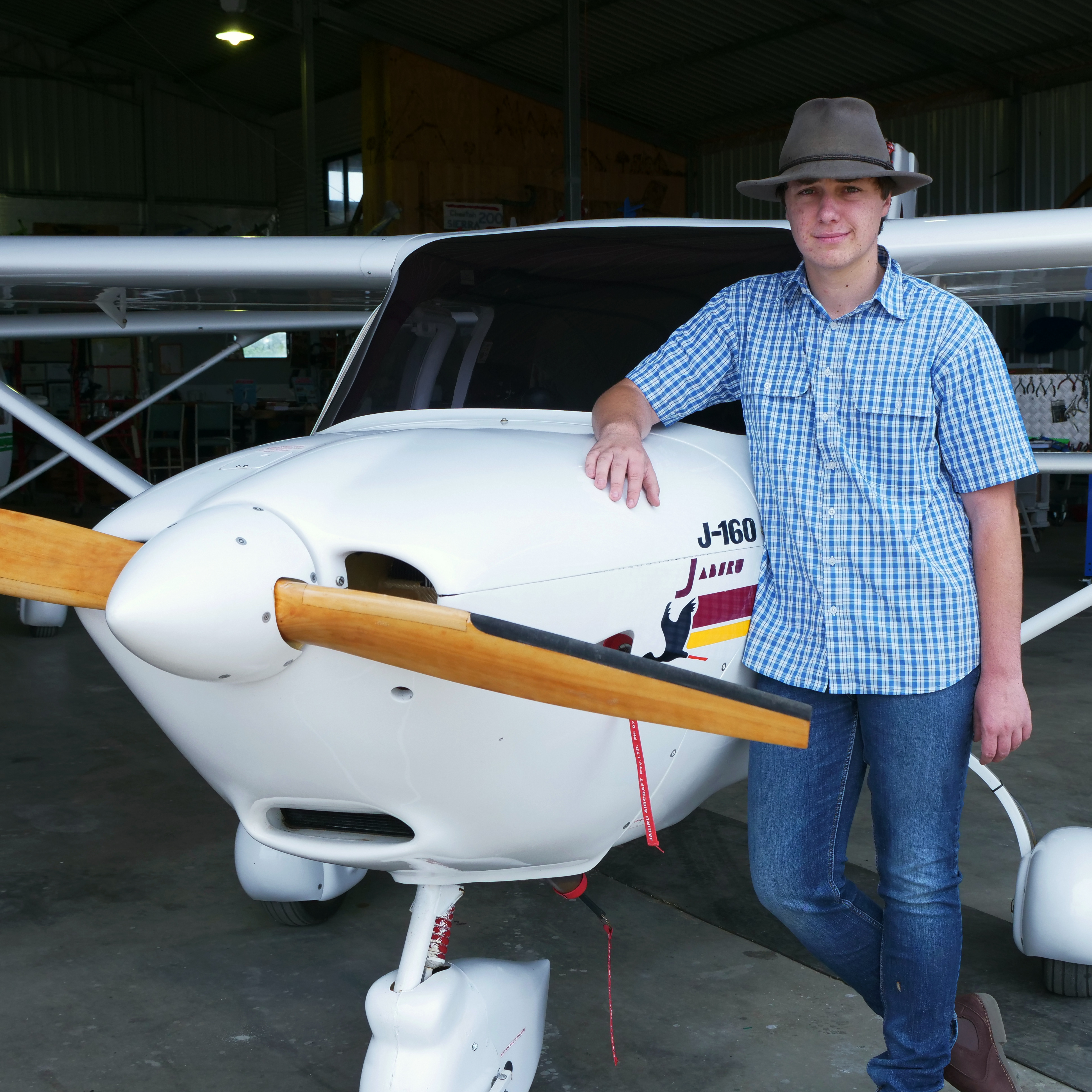 Hayden standing next to a small plane