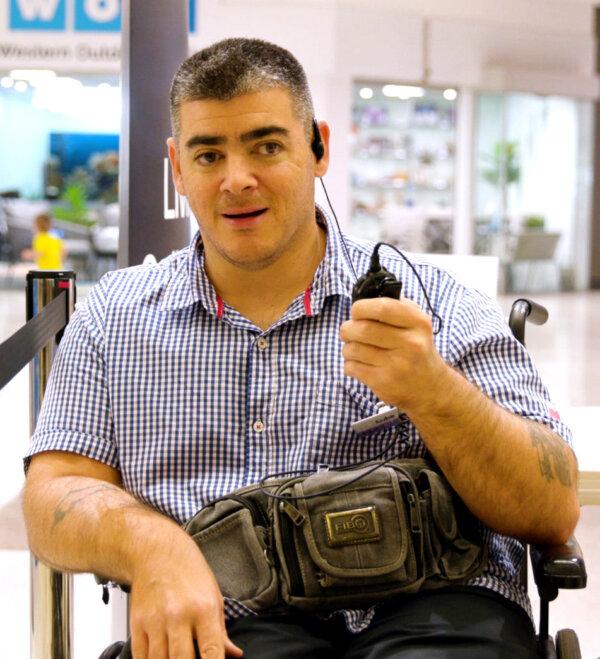 Luke working at Kmart talking to a walkie talkie.